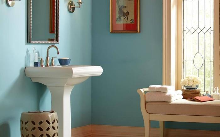 robin's egg blue walls, in a bright room, with a white sink, and a settee in pale beige and white, small bathroom paint colors, framed artwork and a window