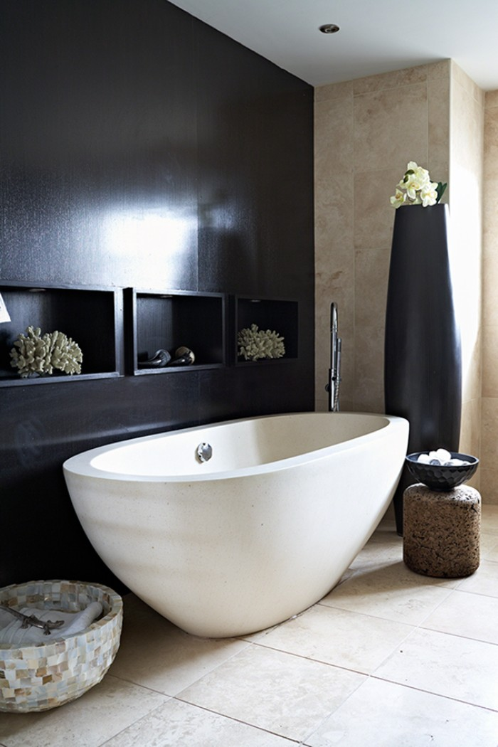 shiny and smoot, black bathroom accent wall, with three inbuilt shelves, near a white bathtub, in a room with walls, covered in beige tiles