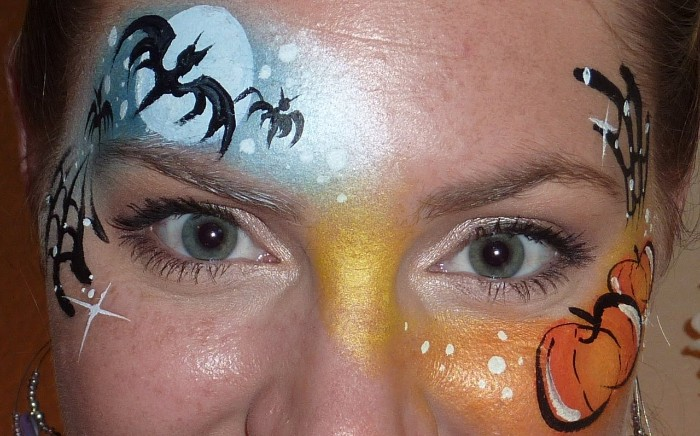 pumpkins and bats, painted on the forehead of a woman, with blue eyes and freckles, halloween face paint ideas for adults, pale blue and orange paint