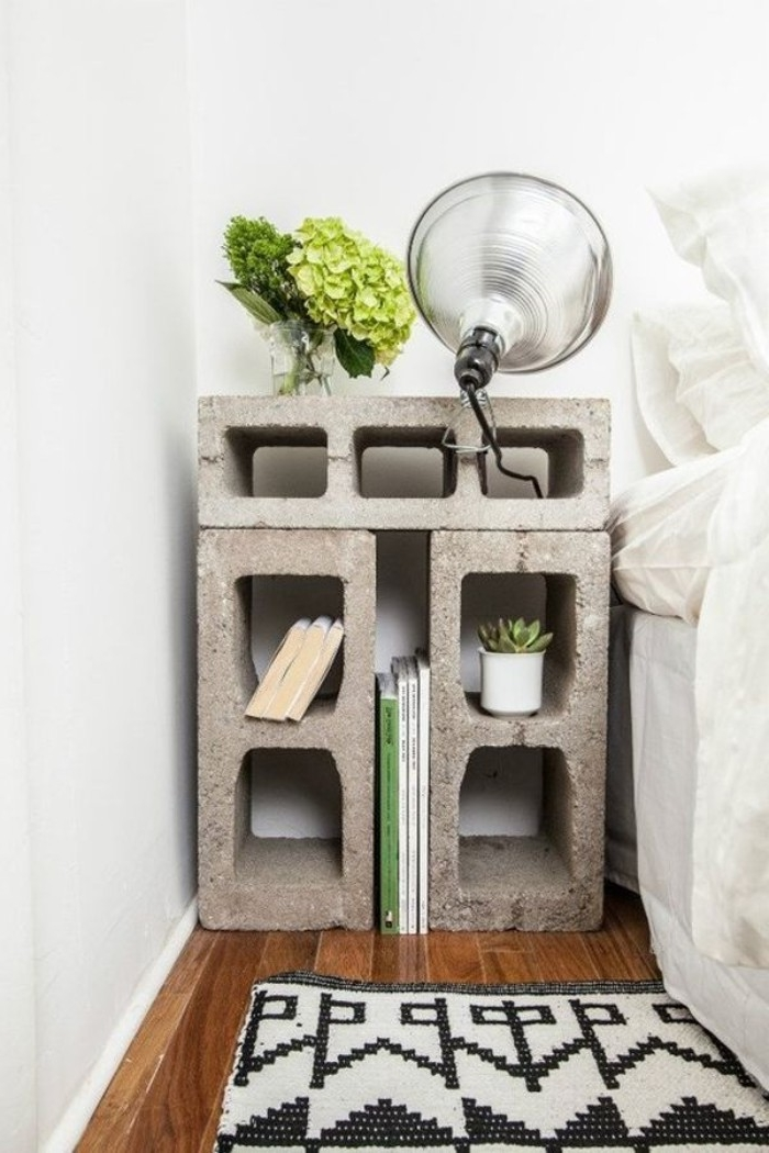 industrial style handmade nightstand, made from three large, grey concrete bricks, with a lamp, books and some flowers