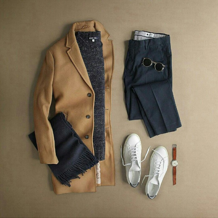 camel colored woolen coat, dark grey sweater, a folded pair of black trousers, white sneakers and a watch, dark grey woolen scarf, and a pair of black sunglasses, wardrobe essentials