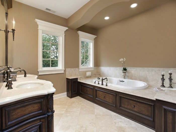 mocha colored bathroom, with dark brown wooden furniture, and pale beige countertops, bathroom color schemes, vintage style inbuilt bathtub and sinks