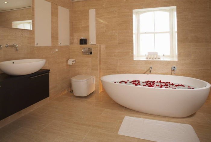 rose petals floating, in an oval white bathtub, filled with water, inside a room, covered with beige tiles