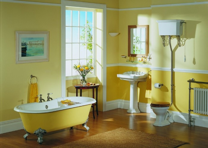 vintage style bathroom, in two shades of yellow, featuring a clafoot bathtub, a toilet and a sink, best paint for bathrooms