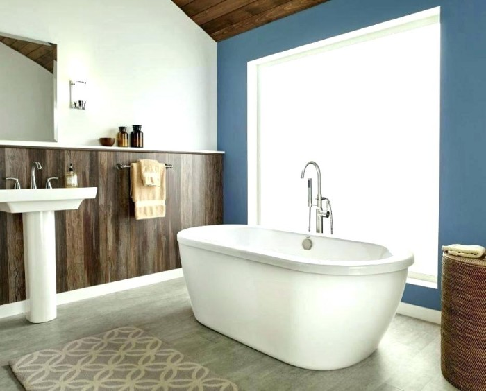 sink and bathtub in white, in a room with white walls, half-covered by dark brown wood paneling, aegean blue bathroom accent wall, pale grey laminate floor