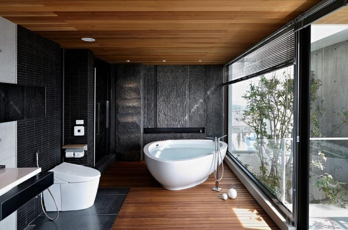 bathroom remodel pictures, room with wooden floor and ceiling, featuring dark grey mosaic tles on the walls, and a white bathtub