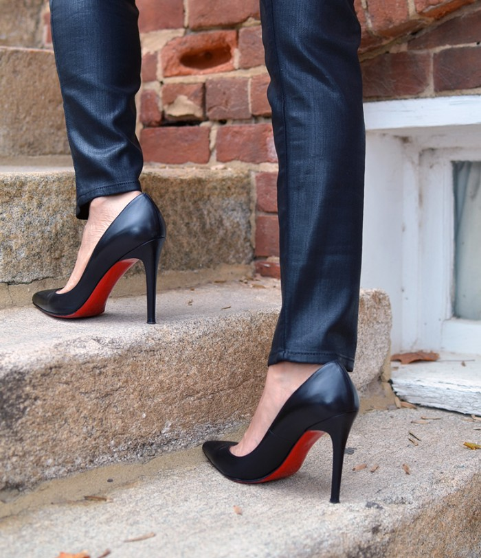 stilettos in black, with red soles, what is a capsule wardrobe, worn by two slim legs, dressed in dark blue jeans