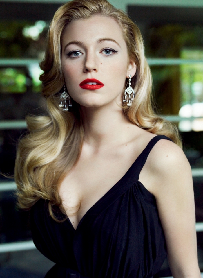 dark navy blue gown, worn by blake lively, with wavy long blonde hair, red lipstick and black mascara, christmas makeup ideas, silver ornamental earrings