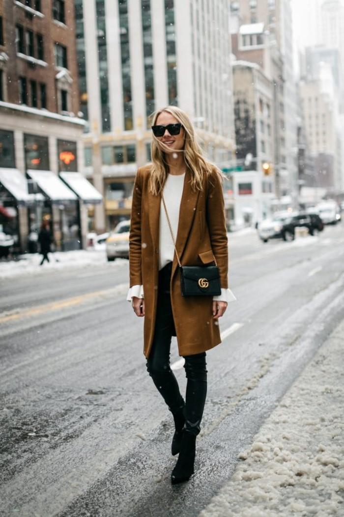 khaki brown wool coat, worn over skinny, black leather trousers, and a plain white jumper, by a smiling blonde woman, with sunglasses and a black, cross body bag