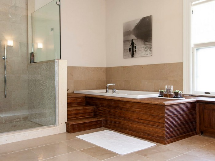 shower cabin near an elevated bath. surrounded by wooden panels, pale beige tiles, bathroom remodel pictures, window and a framed photo