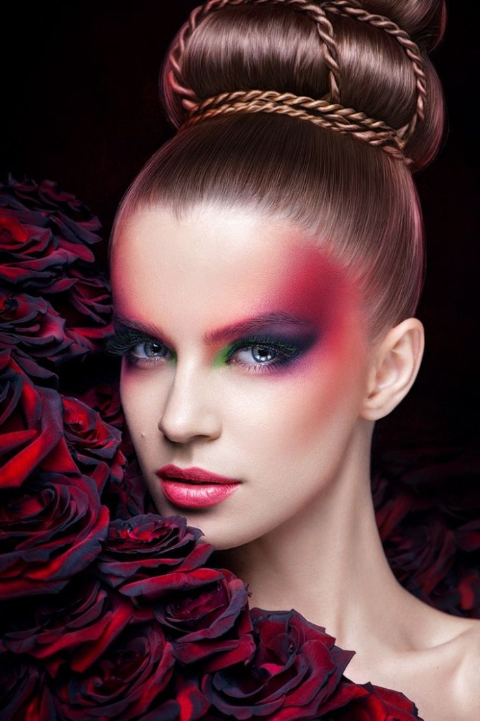 avant-garde christmas eyeshadow, in pink and violet, red and green, worn by a pale young woman, with pink lipstick, and a large ballerina bun