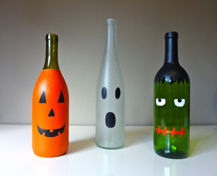glass bottles painted like halloween monsters, an orange jack-o-lantern, a white ghost, and a green frankenstein's monster, halloween party decoration ideas