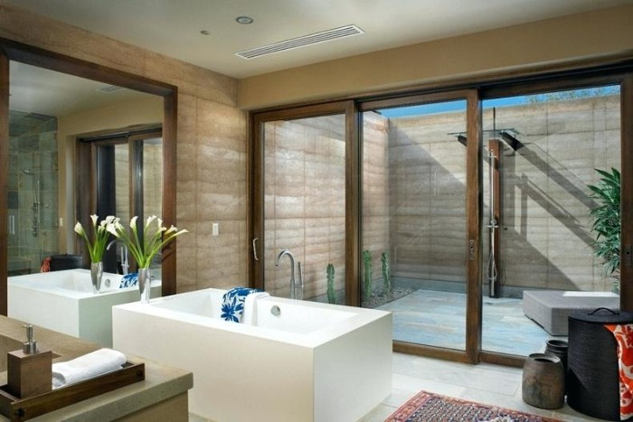 gladiolus bouqet in a clear glass vase, placed near a rectangular white tub, spa like bathrooms, large mirror and a window, overlooking a small private courtyard