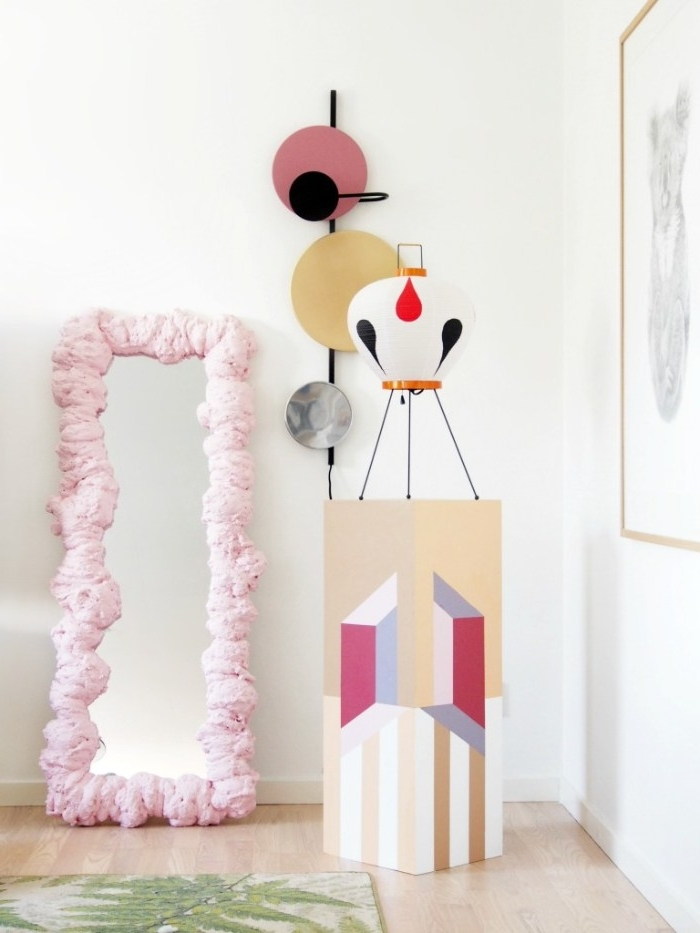 tall mirror with pale, pastel pink frame, made from expanding foam, inside a bright room, decorated with modern art, diys to do at home