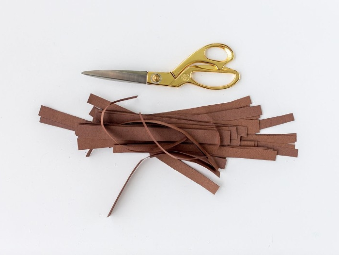strips of brown paper, placed on a white surface, near a pair of scissors, diys for your room, utilizing colorful paper