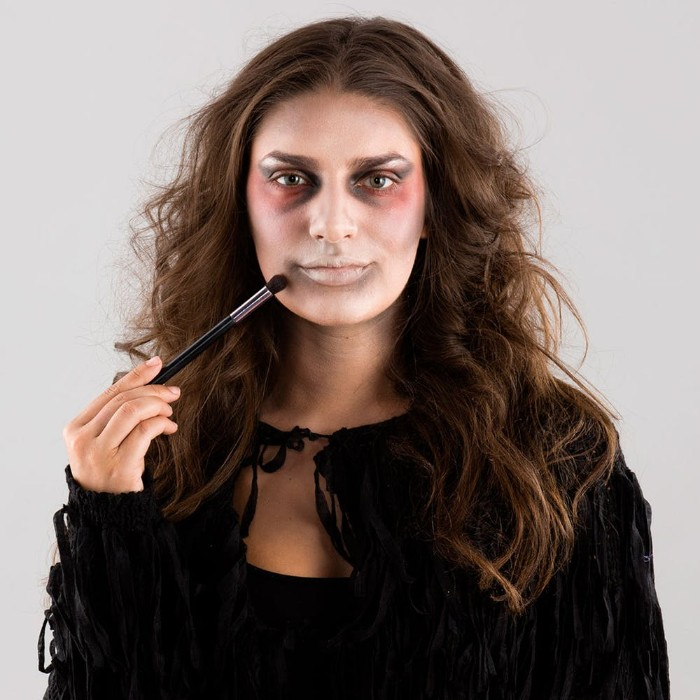 outlining the mouth of a young, brunette woman, using grey makeup and a brush, zombie face paint, and a black tasseled costume
