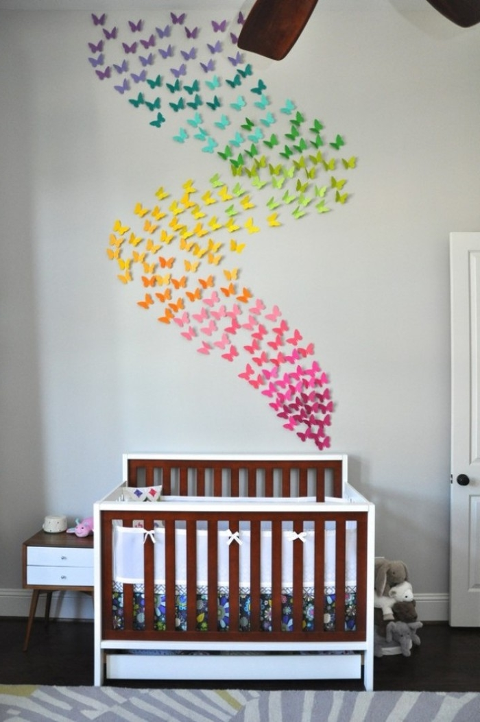 rainbow effect wall decoration, featuring paper butterflies in dfferent colors, hung above a baby crib