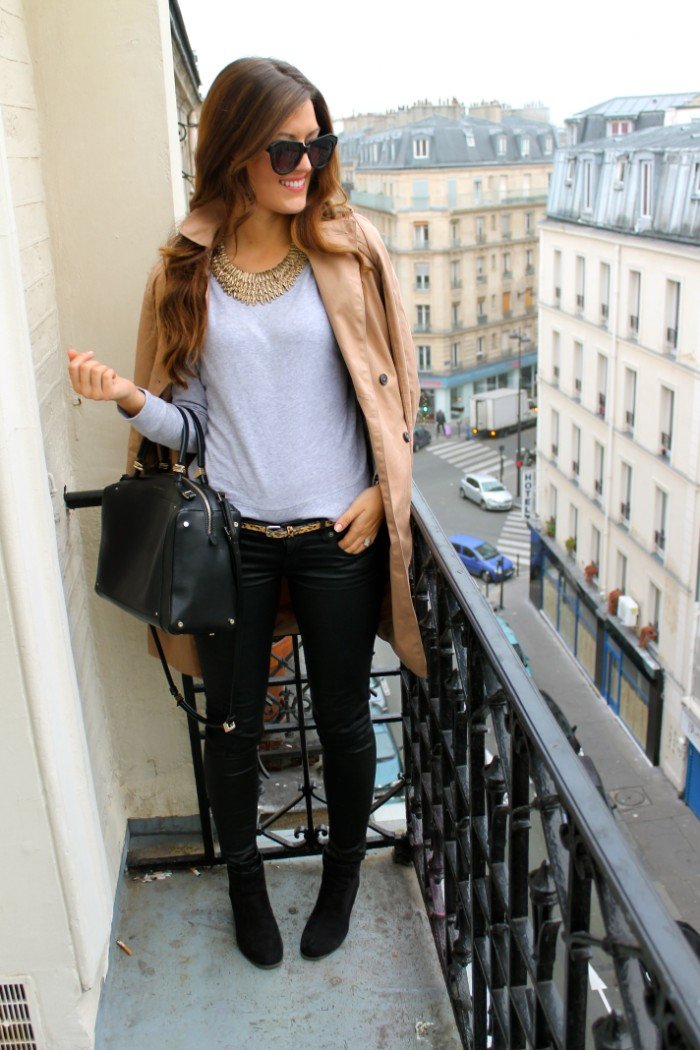 smiling brunette woman, dressed in skinny, black leather trousers, and a pale grey jumper, wardrobe essentials, black ankle boots, classic trench coat, and a black bag