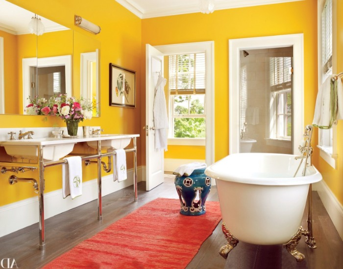clawfooted white bathtub, with gold legs, in a canary yellow bathroom, best bathroom paint colors, with two sinks, and a red runway rug