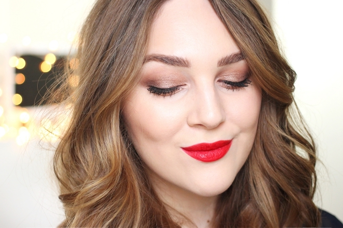 mocha brown christmas eyeshadow, worn with bright red lipstick, by a pale brunette woman, with caramel brown wavy hair