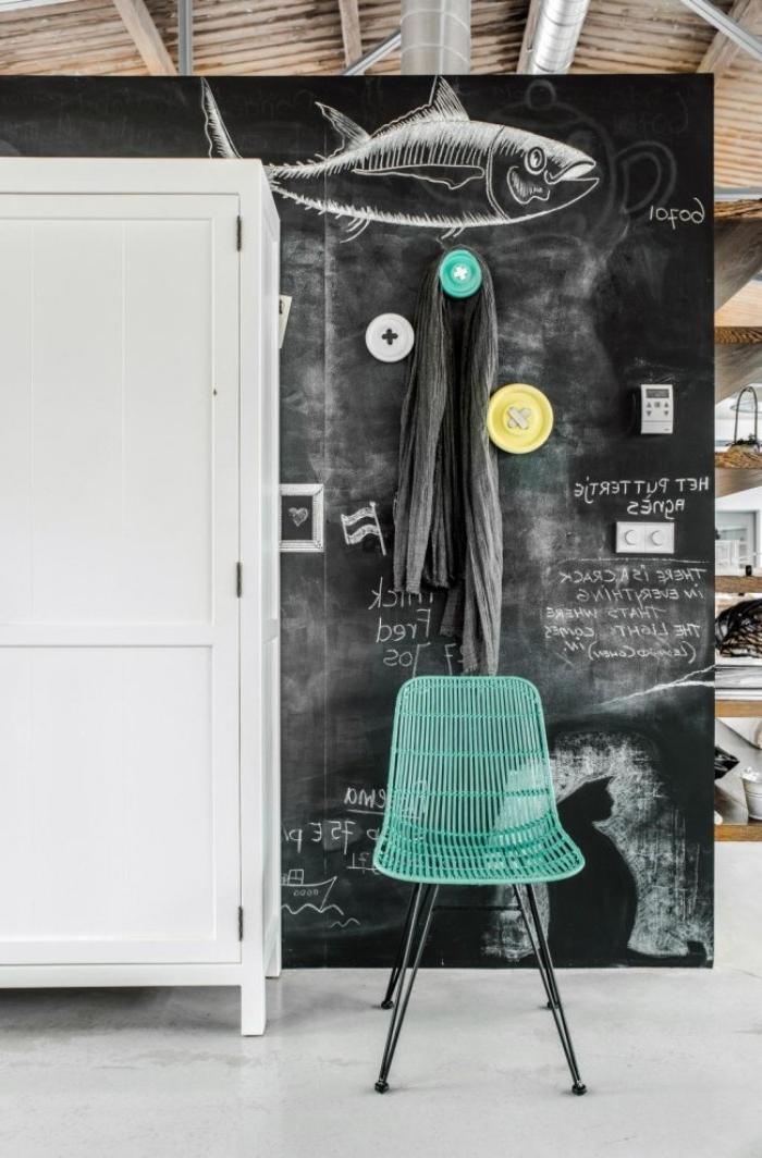 fish drawn with white chalk, on a large blackboard, inside a room with a white floor, and wooden ceiling, teal metal chair, and a white wardrobe