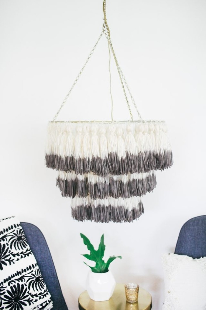 homemdade tassel chandelier, bedroom makeover, hanging from the ceiling of a white room, with two dark grey chairs, and a small metallic table