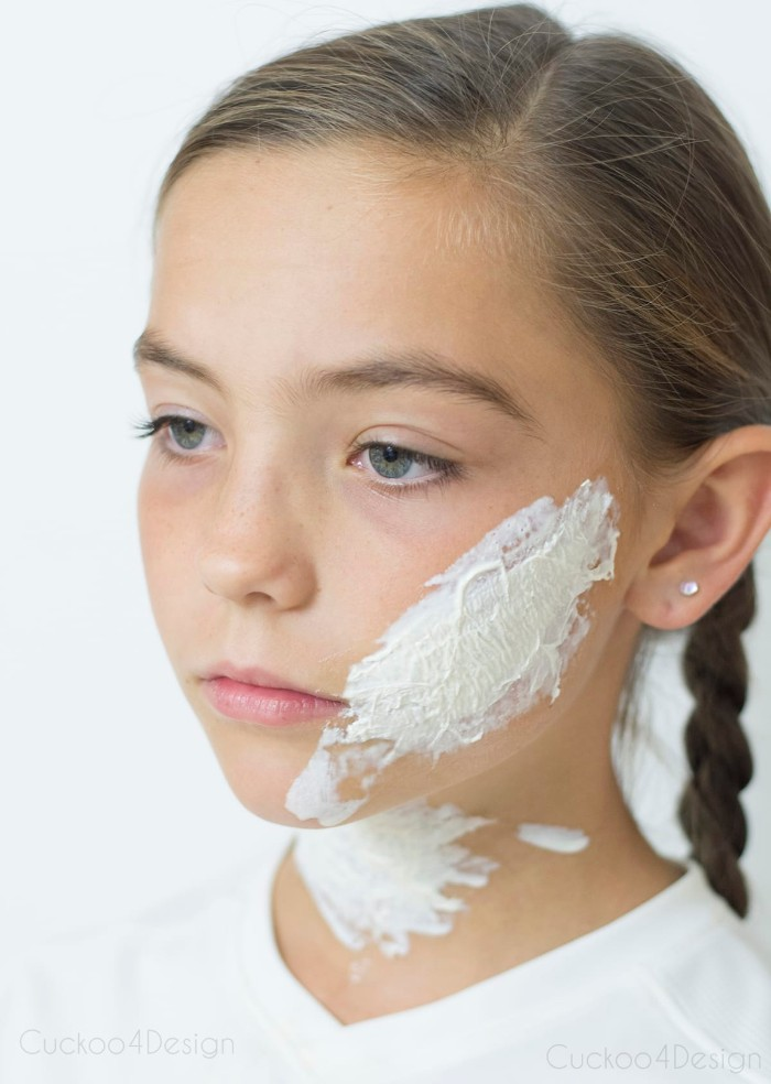 girl with blue eyes, and brunette hair, braided in pigtails, wearing a white t-shirt, special effects makeup wax on her cheek and neck, how to create scary face paint