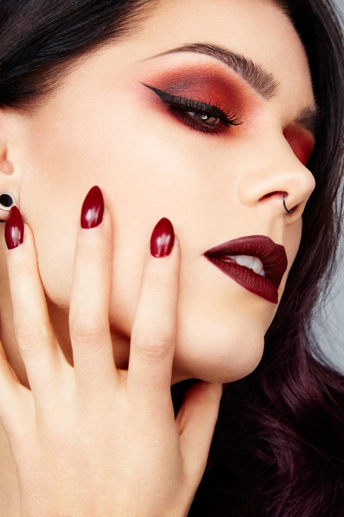 eyeliner in black, and red eye shadow, worn by a pale young woman, with burgundy red lipstick, and a small nose ring, christmas eye makeup, almond shaped nails, painted in dark red nail polish