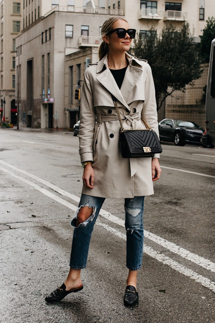 off-white trench coat, worn by a blonde woman, in ripped blue jeans, and a black top, capsule closet