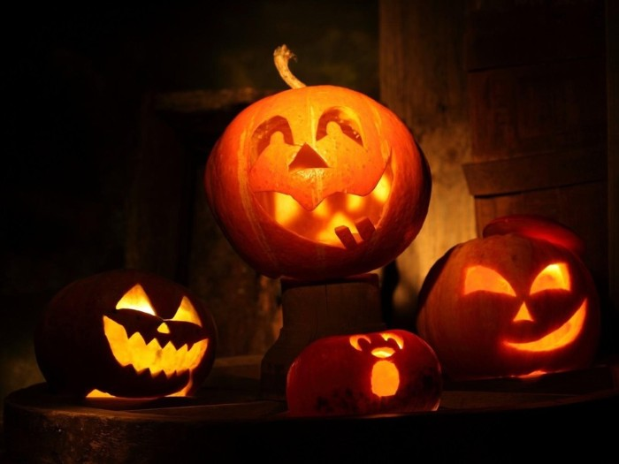 jack-o-lanterns carved from pumpkins, lit with candles from within, four traditional skeleton pumpkin lanterns