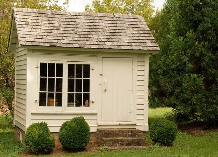 simple small white shed, with grey tiled roof, a double window, and a white door, she shed images, three green shrubs, grass and trees surrounding it