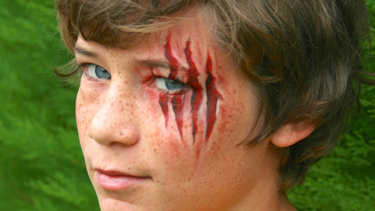 slashed eye wound, realistic claw marks face paint, worn by a young boy, with wavy brunette hair, blue eyes and freckles