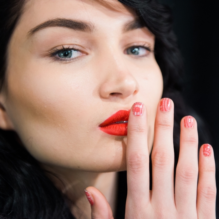 orange lipstick worn by a pale young woman, with black wavy hair, and blue eyes, short manicure with red and white nail polish