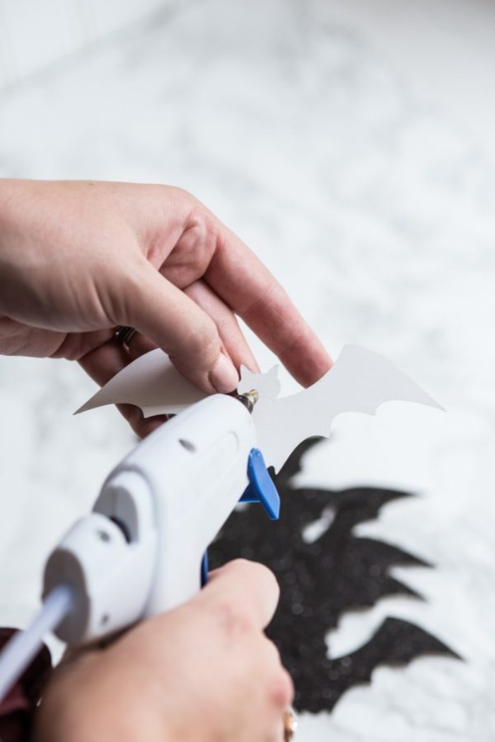 person pouring glue on the back, of a bat-shaped cutout, using a glue gun, more bat shapes in the background