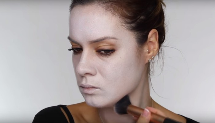 woman applying white powder on her face, using a brush, how to create skeleton face paint, tutorial with photos
