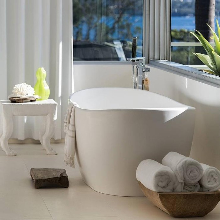 oval white bathtub, inside a room with two windows, and white curtains, master bathroom ideas, a wooden dish with rolled up towels, a small chair with toiletries