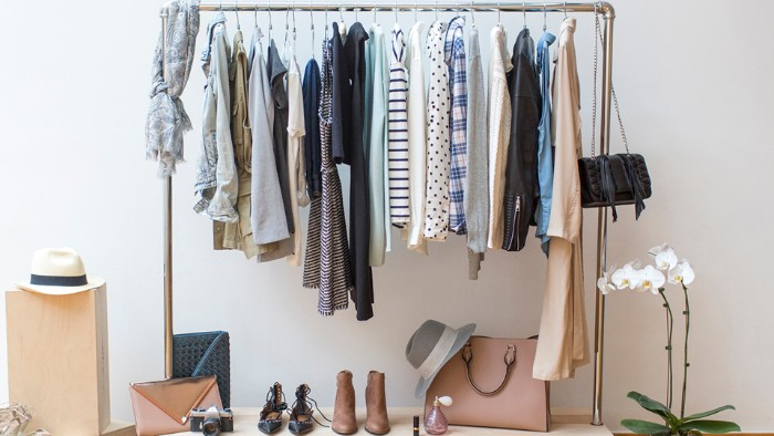 rack made of metal, with a few hangers, containing different clothes, how to create a minimalist wardrobe, shoes and bags nearby