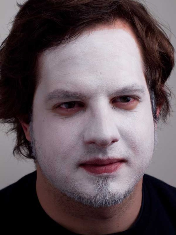 short beard worn by a smiling brunette man, entire face covered in white paint, clown face paint