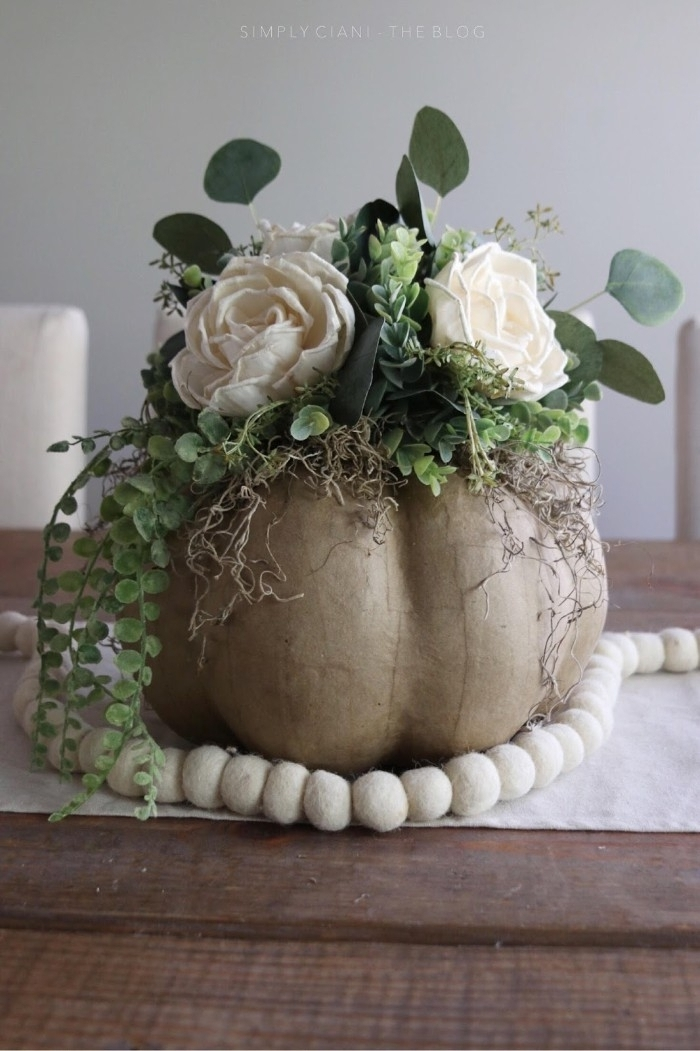 dollar store crafts, papier mache pumpkin in beige, decorated with varous green plastic plants, and faux white roses