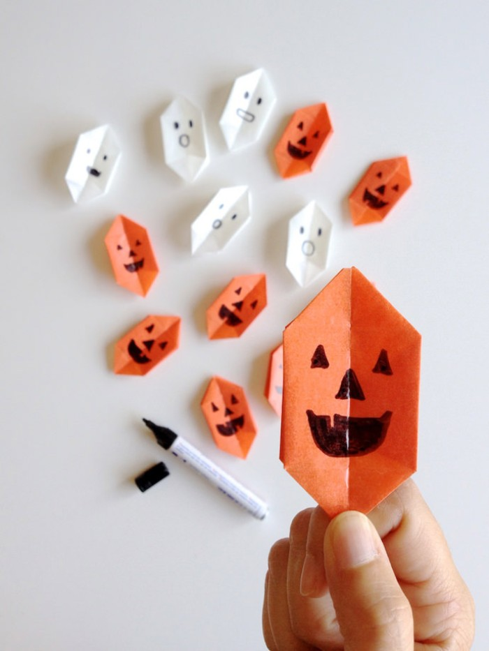smiling jack-o-lantern face, drawn with black permanent marker, on an orange, paper origami shape, more white and orange shapes, and a marker, in tne background