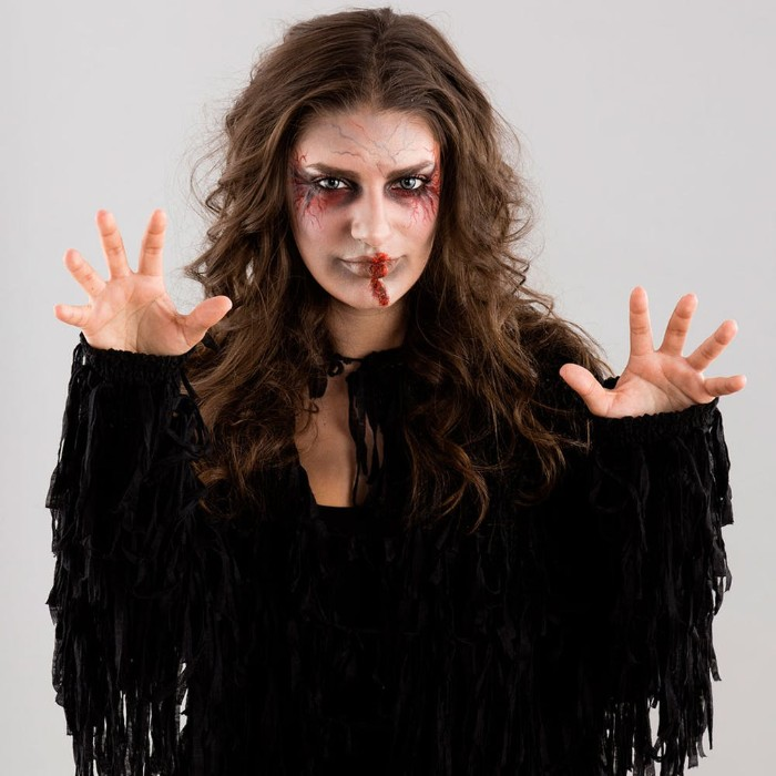 black costume with tassels, worn by a brunette woman, with messy and wavy, long brunette hair, and halloween face paint, featuring fake blood