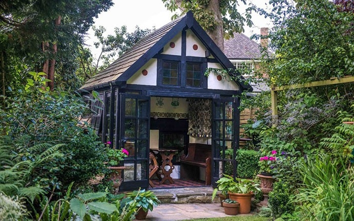 vintage cottage-style garden shed, in black and white, with open glass doors, revealing a rustic interior