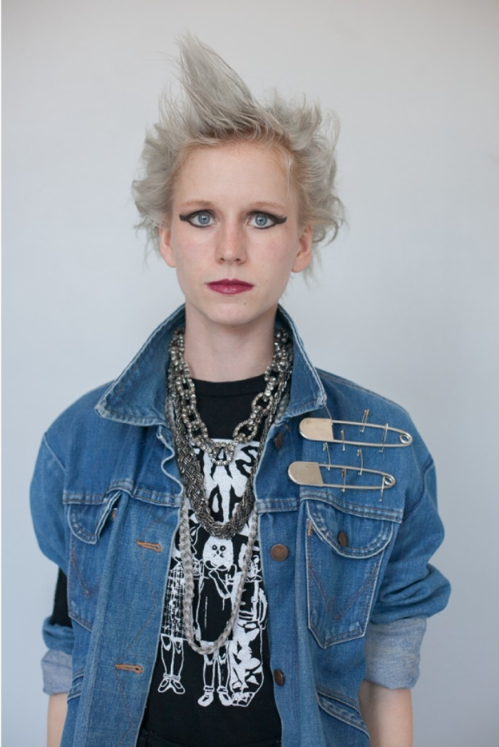 bold black eyeliner, around the eyes of a young woman, with platinum blonde messy hair, and dark red lipstick, couples halloween costume ideas, black t-shirt and denim jacket, with safety pins, and chunky necklaces