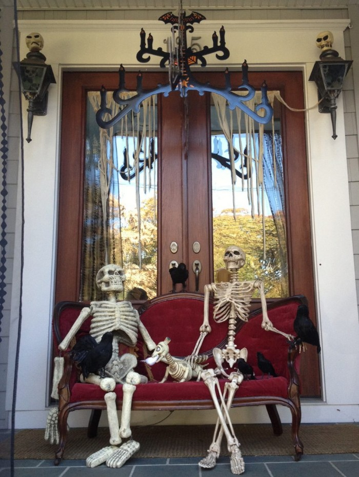 two fake skelettons, sitting on an antique, red velvet settee, with several fake crows, and a skeleton dog, scary outdoor halloween decorations, in front of a double door, decorated with two skulls, and fake cobwebs