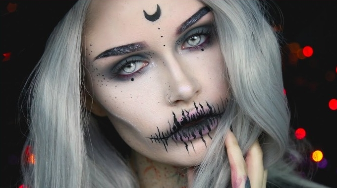 platinum blonde young woman, wearing black and white witch face paint, with a crescent moon on her forehead