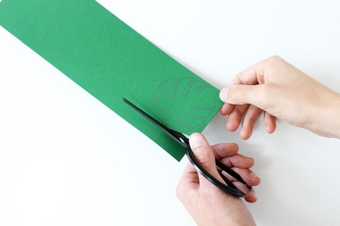 scissors held by a pale hand, cutting along the lines of a palm leaf shape, drawn in pencil, on a piece of green card, held by another hand, how to decorate a bedroom, using arts and crafts