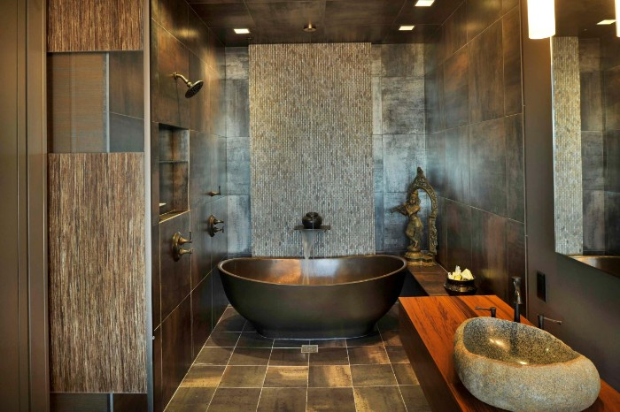 brown and dark grey walls and floor, inside a room, containing a dark grey bathtub, master bath remodel, sink made from a piece of stone
