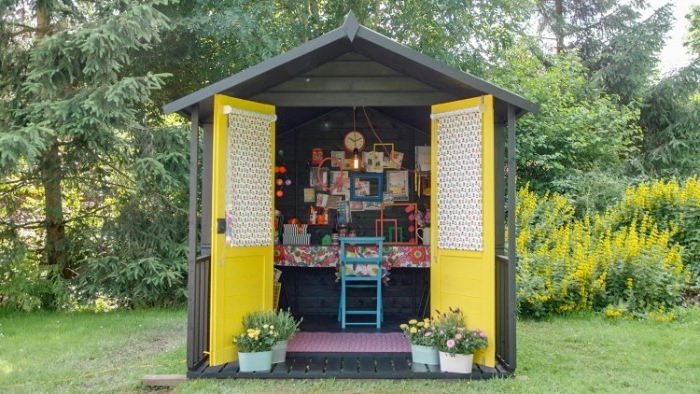 wide open yellow doors, attached to a small, dark grey she shed, desk and chair, and lots of colorful frames visible inside