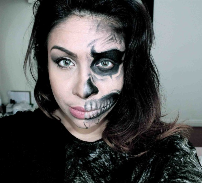 teenage girrl with dark hair, wearing skeleton face paint on one half of her face, the other half is left bare