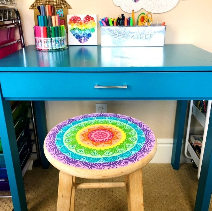 desk in blue, near a round wooden stool, decorated with a rainbow-colored flower mandala, diy room decor, pencil holders and colorful stationary